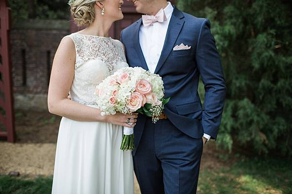 details of the bridal gown and bouquet with pink roses and white hydrangea. The pink roses match the grooms pink bowtie.