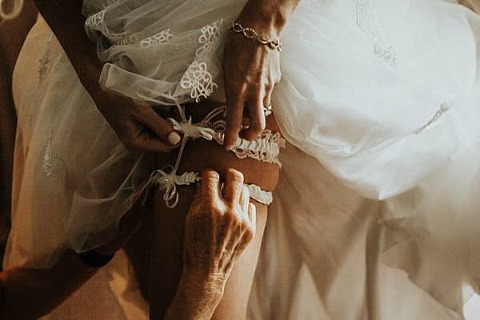 bride putting on her garter belt. Image by We Are The Cashmans