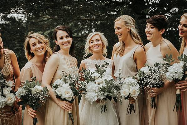 Bridal party is light pink and gold mismatched bridesmaids dresses.