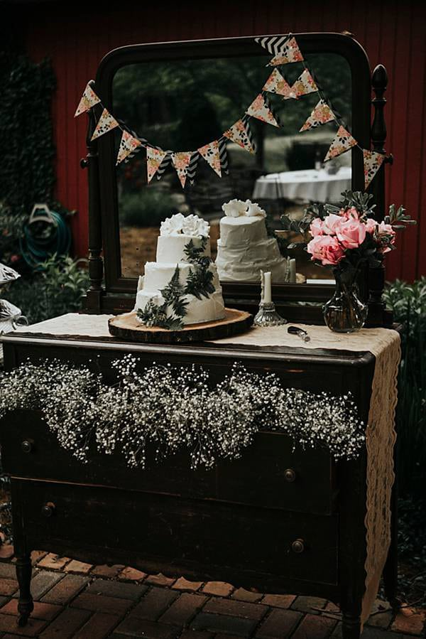 A vintage dresser and mirror were used for the cake table. The table is decorated with paper, roses, lace and babies breath.