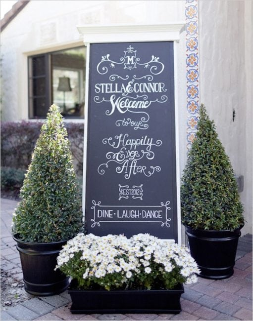 Potted Boxwoods and Daisies flank the welcome sign to the reception. Image courtesy of jenniferpoyntnerflowers.co.uk